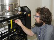 Thomas Clawson, NCC Brewing, Distillation and Fermentation Instructor, adjusts the flow path of the Brew-Magic system in the College's lab.